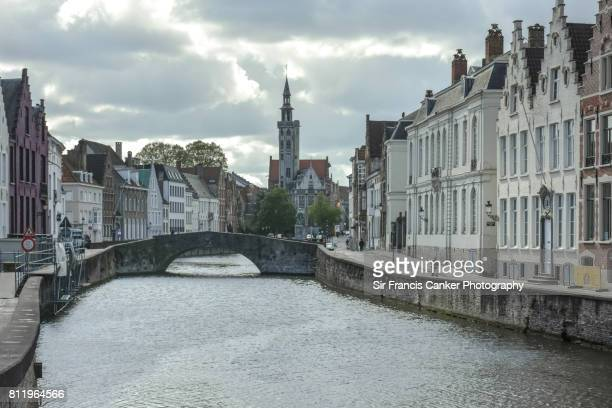 'Spiegelrei' and 'Spinolarei' canal with 'Poortersloge' tower ('Burghers' Lodge') on background and dramatic sky in Bruges, Flanders, Belgium, a UNESCO heritage site