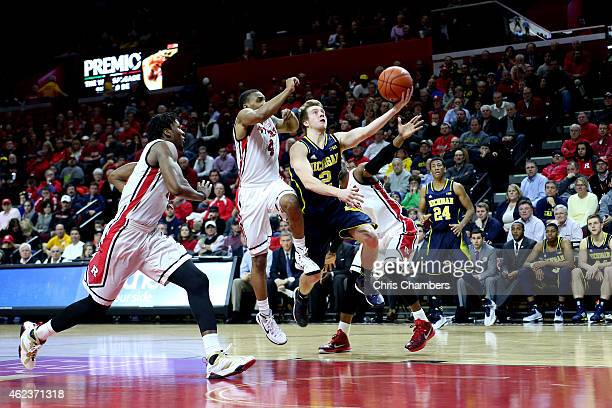 Spike Albrecht of the Michigan Wolverines drives for a shot attempt against Myles Mack of the Rutgers Scarlet Knights during their Big Ten conference...