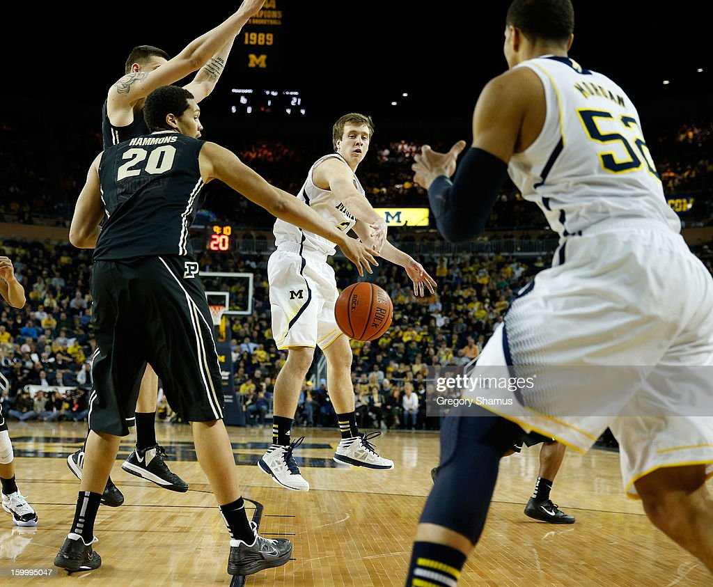 Spike Albrecht #2 of the Michigan Wolverines passes to Jordan Morgan #52 around the outstretched arm of A.J. Hammons #20 of the Purdue Boilermakers during the first half at Crisler Center on January 24, 2013 in Ann Arbor, Michigan. Michigan won the game 68-53.