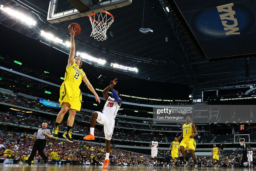 Spike Albrecht #2 of the Michigan Wolverines shoots against Michael Frazier II #20 of the Florida Gators in the second half during the South Regional Round Final of the 2013 NCAA Men's Basketball Tournament at Dallas Cowboys Stadium on March 31, 2013 in Arlington, Texas.