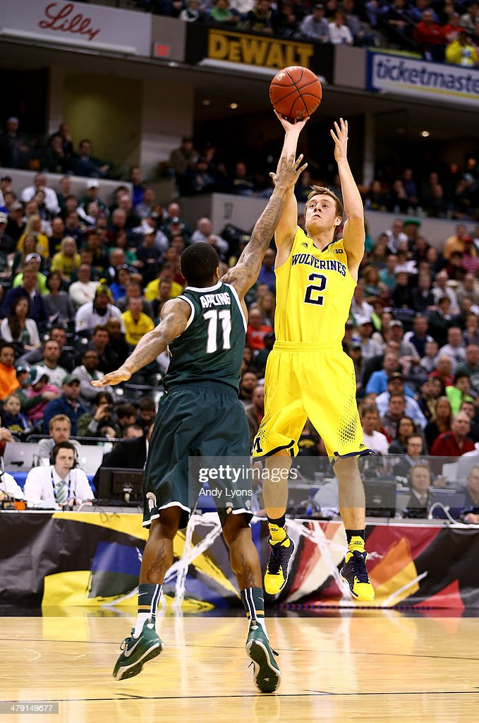 Spike Albrecht of the Michigan Wolverines takes a shot over Keith Appling of the Michigan State Spartans during the 2014 Big Ten Men's Championship...