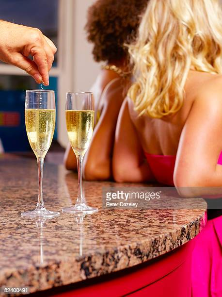 Spiking girls champagne drinks in bar.
