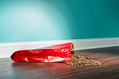 A low angle view of a red paper bag of dog food spilled on a hardwood floor. There is kibble scattered on the hardwood floor with a white baseboard and green wall in the background