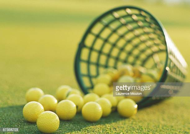 Spilled basket of yellow golf balls, close-up