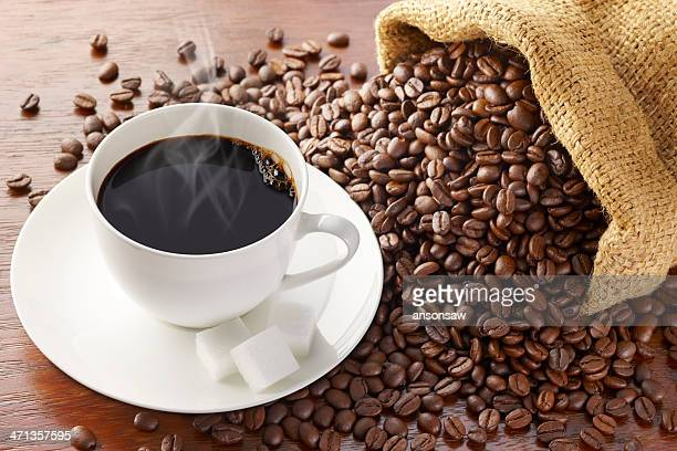Spilled coffee beans surround saucer with coffee and sugar