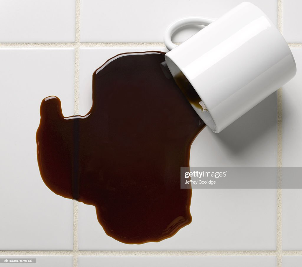 Spilled cup of coffee on tile floor, studio shot : Stock Photo