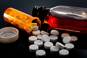 Opioid epidemic, drug abuse and dangerous mixing of barbiturates and alcohol concept with oxycodone pills fallen out of a prescription pill bottle next to a flask of hard liquor