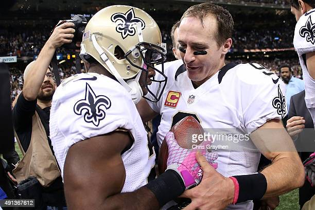 J Spiller hands Drew Brees of the New Orleans Saints the ball after scoring a touchdown on Brees' 400th Touchdown Pass at MercedesBenz Superdome on...