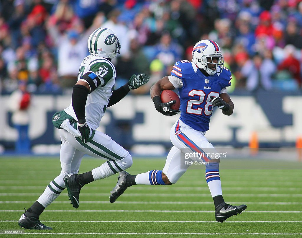 C.J. Spiller #28 of the Buffalo Bills runs past Yeremiah Bell #37 of the New York Jets at Ralph Wilson Stadium on December 30, 2012 in Orchard Park, New York.