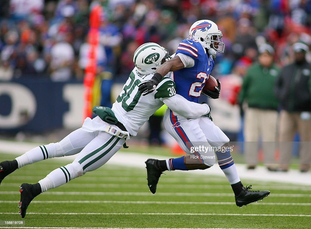 C.J. Spiller #28 of the Buffalo Bills runs with LaRon Landry #30 of the New York Jets hanging on at Ralph Wilson Stadium on December 30, 2012 in Orchard Park, New York.