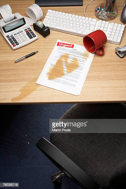 Spilt coffee on documents on desk, elevated view