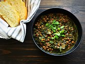 A bowl of spinach and lentil soup with slices of bread on the side shown on a dark wood background