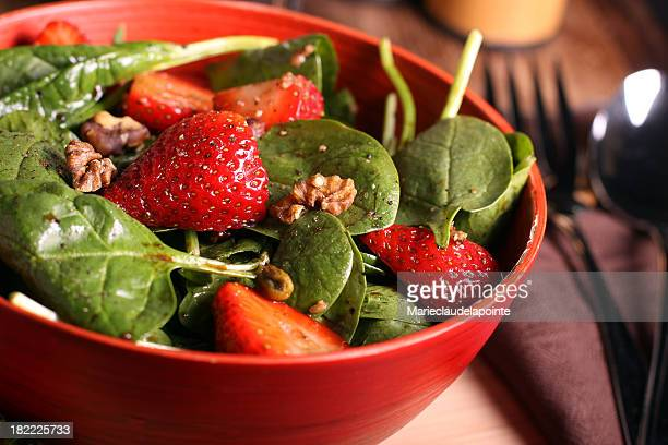 Spinach and strawberry salad in red bowl