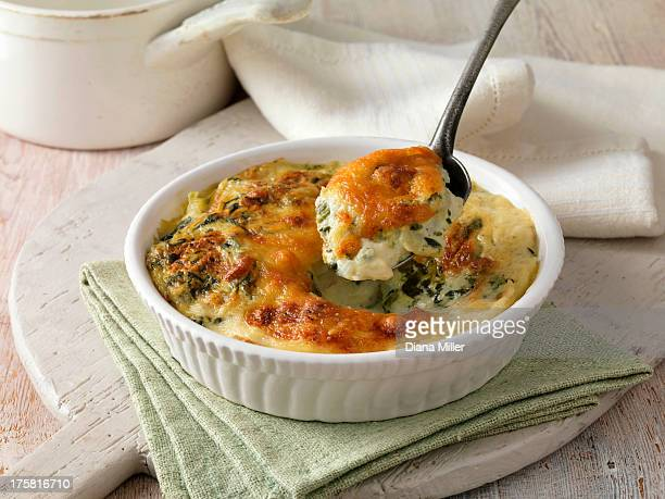 Spinach gratin in a white dish with metal spoon on green cloth