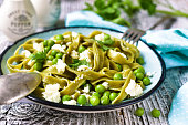 Spinach pasta with green pea and cheese on old wooden background.