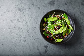 Spinach salad with dried cranberries and pomegranate seeds; seen from above