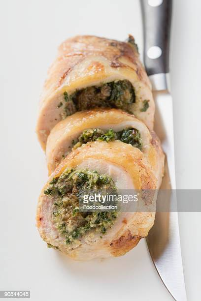 Spinach stuffed chicken roulade with knife, close up
