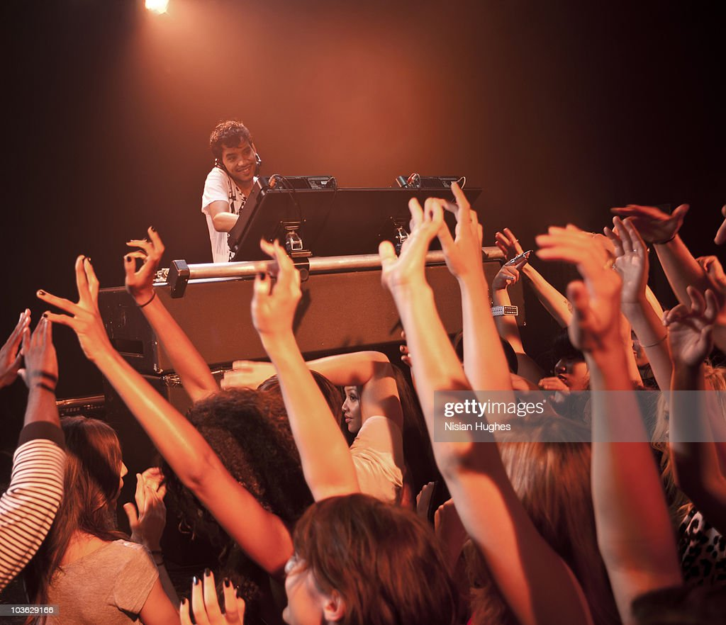 DJ spinning at nightclub surrounded by crowd : Stock Photo