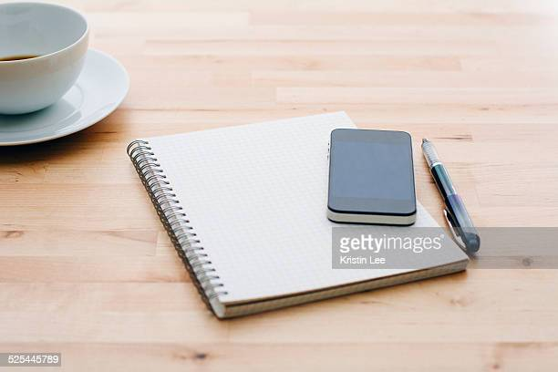 Spiral notebook, Ballpoint pen, Mobile phone and coffee cup on wooden table
