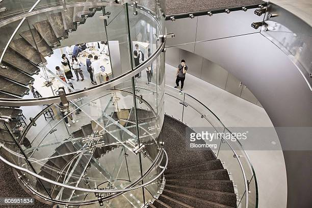 A spiral staircase leads to the product display area as customers shop at the Apple Store inside the IAPM shopping mall in Shanghai China on Friday...