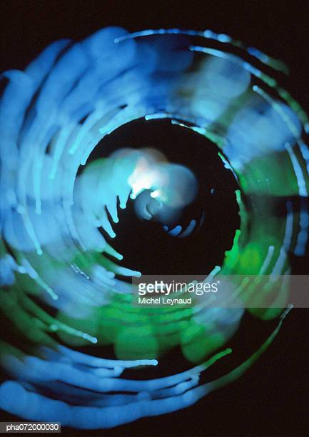 Spiraling light effect, blues and greens, black background