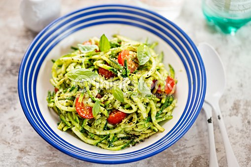 Spiralled courgette spaghetti with green pesto and cherry tomatoes : Stock Photo