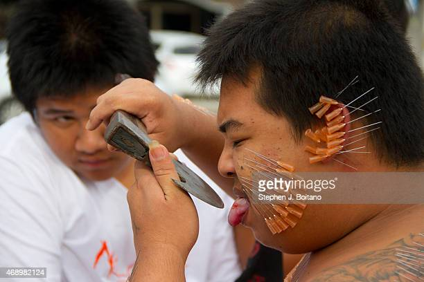 A spirit medium walk in a street procession through Phuket Town as part of the Phuket Vegetarian Festival in Phuket Town ThailandThe event is held...