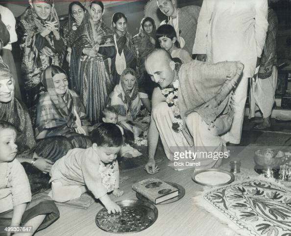 Spiritual leader of Hare Krishna's Avenue Rd temple Visvakarma conducts test with 6monthold child to see whether baby will choose the book or money...