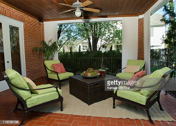 A splash of color and outdoor furniture fill a covered porch at this home in Mission Hills Kansas that was given a patio makeover