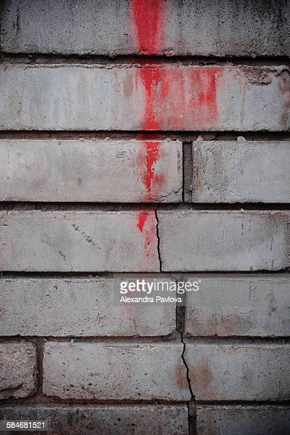 Splash of red on a cracked grey wall