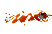 Blots of caramel and teaspoon dipped in caramel. isolated on white background. flat lay, top view