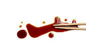 wooden chopsticks dipped in soy sauce spilled. splashes and drops of isolated on white background. flat lay, top view