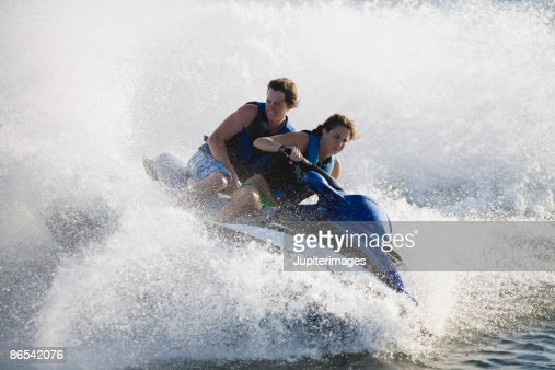 Splashing couple riding jet ski
