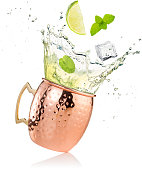 splashing moscow mule cocktail in copper mug isolated on white