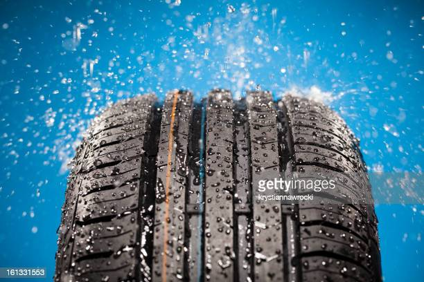 Splashing water on new wet tire against blue background
