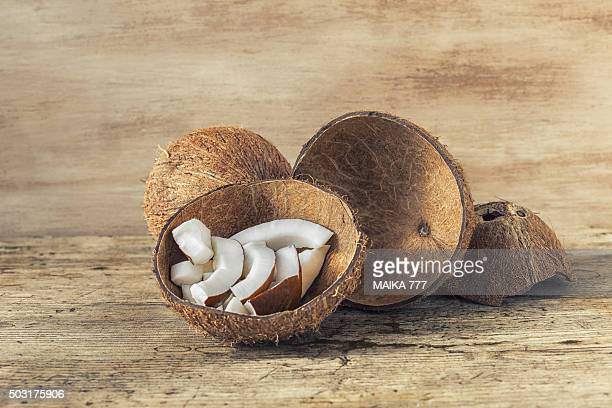 Split coconuts on wooden table, close-up.