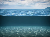 Conceptual split-shot of the deep blue sea with seabed and dark stormy sky.