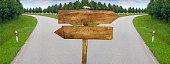 Splitting road with blank crossroad wooden blabk signs