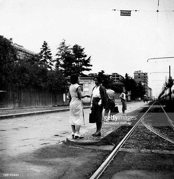 Spme Italian people waiting for the tram at a suburban stop Milan 1950s