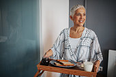 Mature woman holding a breakfast tray
