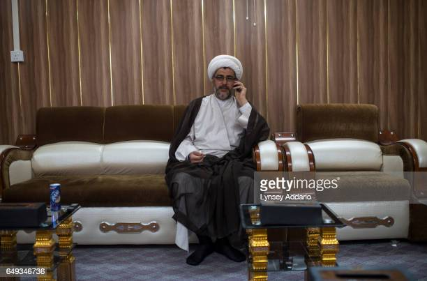 Spokesman for Shiite leader Muqtada al Sadr Sheikh Salaah receives a phone call during an interview in Najaf Southern Iraq June 22 2014 As Iraq...