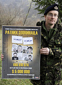 spokesman Ian Pratt holds a wanted poster for indicted war criminals Radovan Karadzic and Ratko Mladic and Goran Hadzic and Stojan Zupljanin after a...
