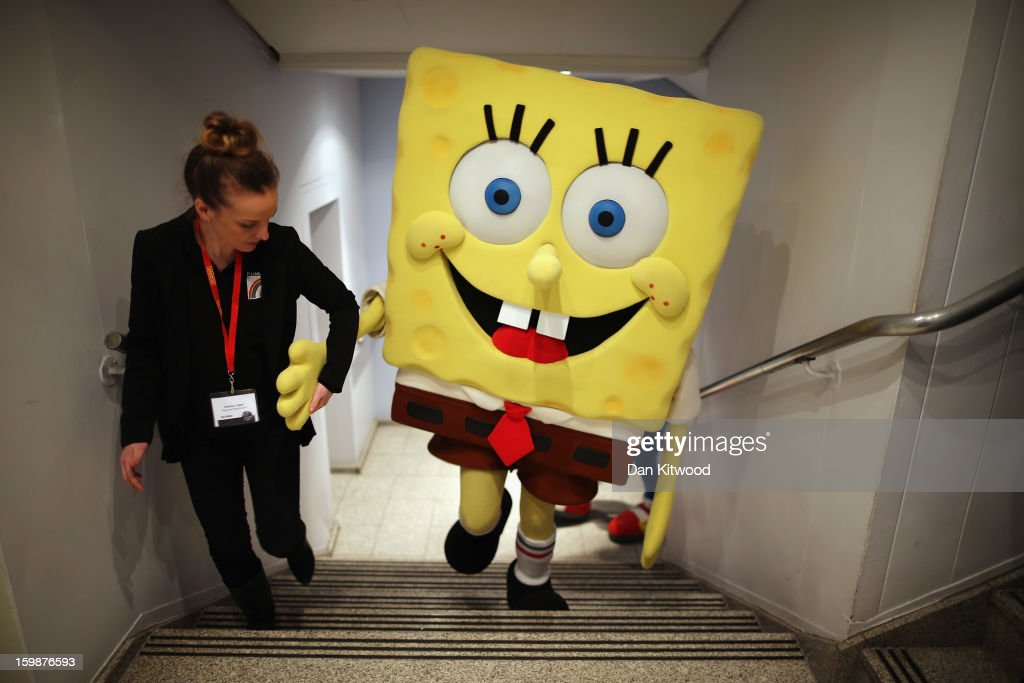 A Sponge Bob Square Pants character is helped up a flight of stairs during the 2013 London Toy Fair at Olympia Exhibition Centre on January 22, 2013 in London, England. The annual fair which is organised by the British Toy and Hobby Association, brings together toy manufacturers and retailers from around the world.