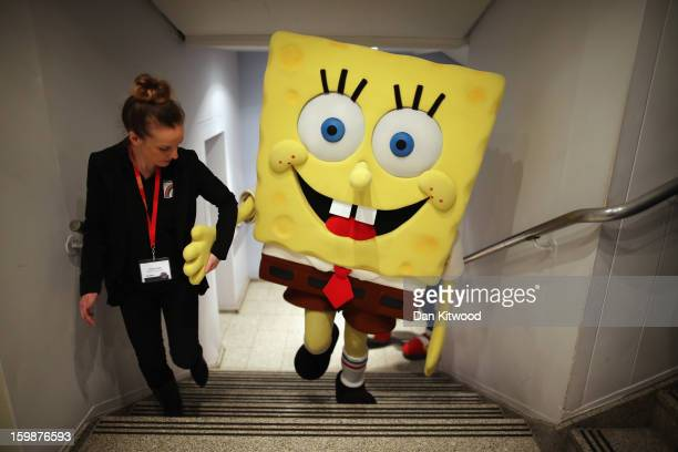 Sponge Bob Square Pants character is helped up a flight of stairs during the 2013 London Toy Fair at Olympia Exhibition Centre on January 22 2013 in...