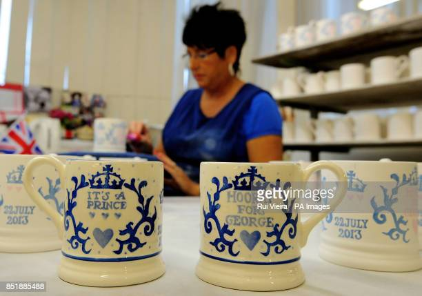Sponge decorator Lynn Lovatt puts the finishing touches to a batch of commemorative Royal Baby mugs for Prince George of Cambridge as they go into...