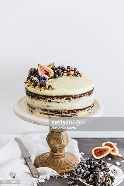 Sponge layered cake topped with fruit on a cake stand