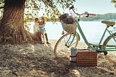 A pastel colored bicycle with a basket full of picnic goodies and a cute couple cuddling under a tree.