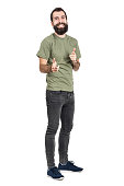 Spontaneously laughing bearded man in green t-shirt pointing fingers at camera. Full body length portrait isolated over white studio background