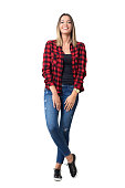 Spontaneously laughing relaxed young pretty casual woman in jeans and plaid shirt. Full body length standing portrait isolated over white background.