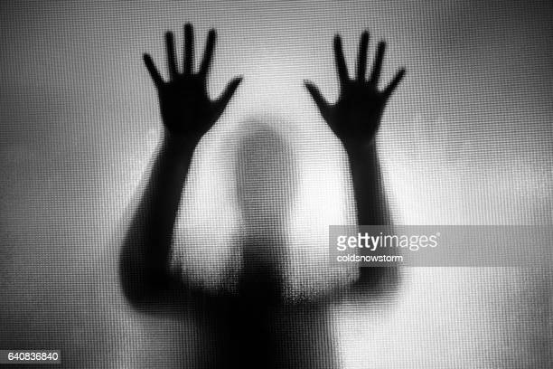 Gruselige verzerrte Silhouette einer Frau mit ihren Händen auf Glasscheibe gelegt